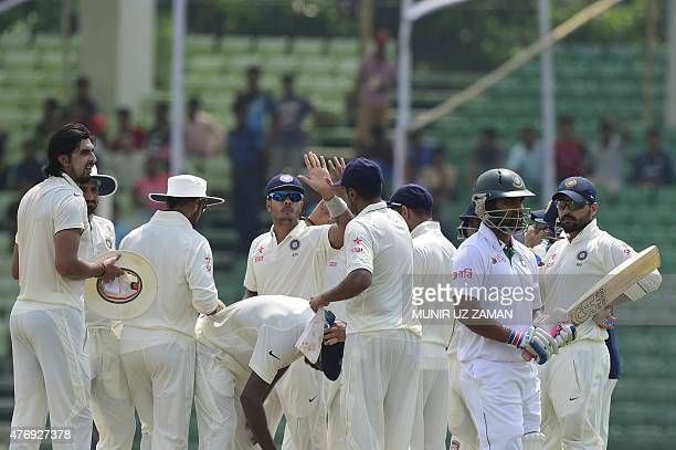 Bangladesh cricketer Tamim Iqbal walks off the field after being dismissed by Indian wicketkeeper Wriddhiman Saha during the fourth day Test match...