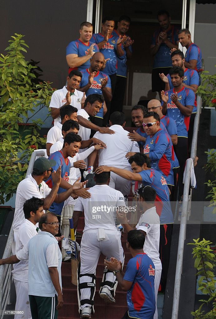Bangladesh cricketers and Bangladesh Cricket Board offcials congratulate Imrul Kayes and Tamim Iqbal as they walk into the pavilion after the fourth...