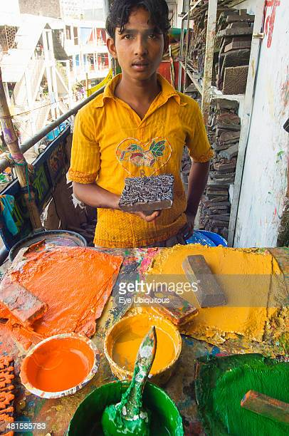 Bangladesh Dhaka Young man holding a printing block used to print on cotton fabrics in New Market with palettes of colors in front of him