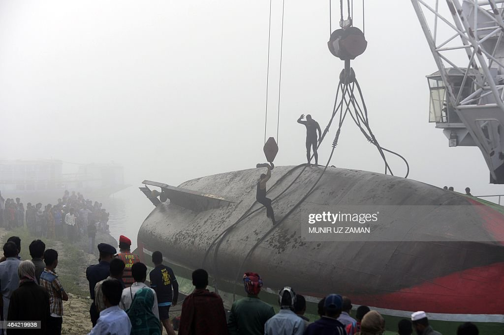 Bangladesh fire service scuba divers stand on a ferry as they try to fix wires from a crane to lift it after it capsized at Paturia some 70 kms east of Dhaka on February 23, 2015. The death toll in a ferry accident in central Bangladesh soared to 69 on February 23, after more bodies were recovered from the overcrowded boat which sank within minutes of colliding with a cargo vessel. AFP PHOTO/Munir uz ZAMAN