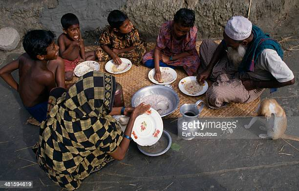 Bangladesh Khulna Char Kukuri Mukuri Family having breakfast of rice seated on mat laid on ground and eating with their right hands