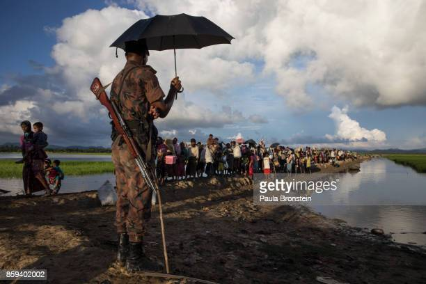 Bangladesh oder guards stand by as thousands of Rohingya refugees fleeing from Myanmar walk along a muddy rice field after crossing the border in...