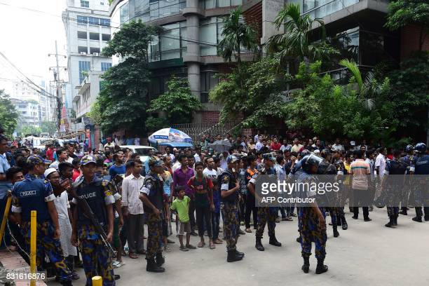 Bangladesh police officials stand guard as bystanders gather at the scene of an operation to storm an alleged militant hideout in Dhaka on August 15...