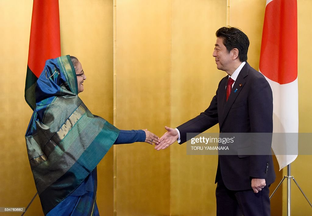 Bangladesh Prime Minister Sheikh Hasina (L) is welcomed by Japanese Prime Minister Shinzo Abe (R) prior to their talks in Nagoya, central Japan, on May 28, 2016. Hasina came to Japan to attend the Group of Seven (G7) summit meeting in Ise. / AFP / POOL / TORU