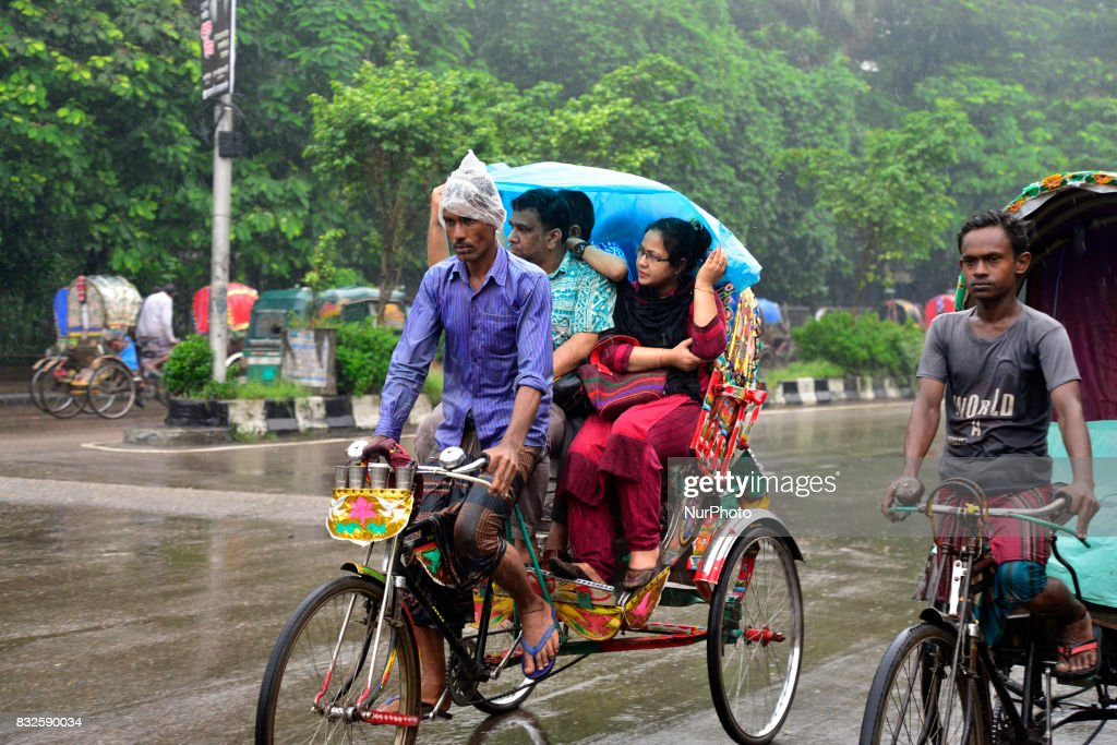 Bangladesh rickshaw drives with passenger on the street during rainy day in Dhaka, Bangladesh. On August 16, 2017