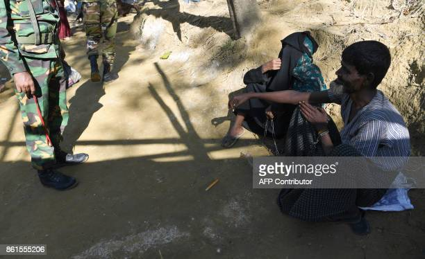 Bangladesh soldiers attempt to speak with Rohingya refugee Ali Hussain as he is restrained by his sister with a metal chain at Balukhali refugee camp...