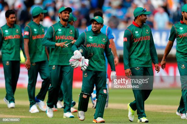 Bangladesh wicket keeper Mushfiqur Rahim walks off the pitch with his teammates after losing the ICC Champions Trophy semifinal cricket match between...