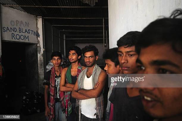 BangladeshhealthrightsgarmentFEATURE by Shafiq Alam Bangladeshi garment labourers pose in a sandblasting factory in Dhaka on August 4 2011...