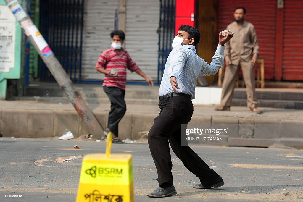 A Bangladeshi activist from Jamaat-e-Islami throws a stone during a protest in Dhaka on February 12, 213. The protesters hurled home-made bombs and attacked vehicles with bricks as police fought back with rubber bullets and tear gas in Dhaka's busy Karwan Bazaar and Motijheel commercial districts, police and witnesses said. AFP PHOTO/ Munir uz ZAMAN