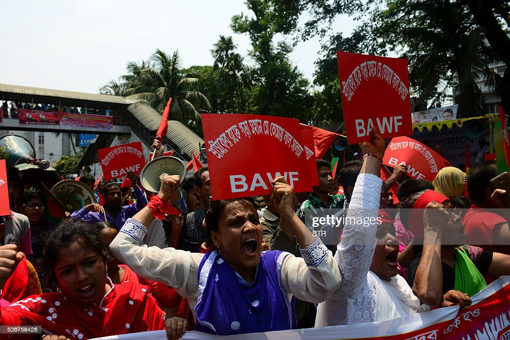 Bangladeshi activists and workers shout slogans and wave flags during a procession to mark May Day or International Workers Day in Dhaka on May 1, 2016. Activists around the world mark international workers' day with marches demanding better working conditions, more jobs and higher wages. / AFP / STR