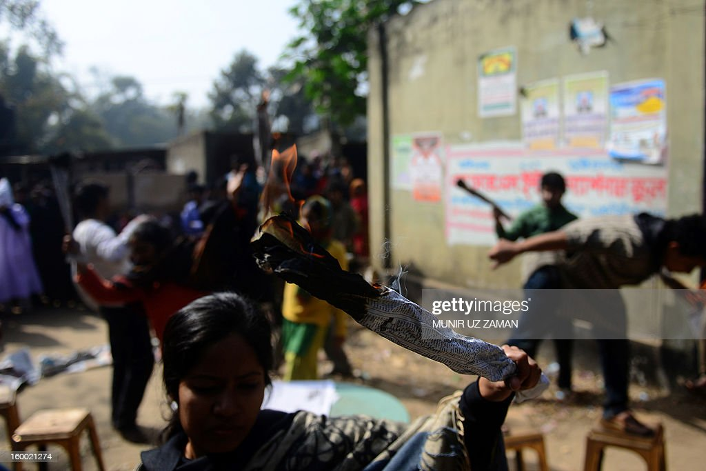 Bangladeshi activists perform a street drama during a protest demanding punishment for the Tazreen Fashion factory owner and compensation for the victims of the 2012 factory fire, in Savar, some 30 kilometres north of Dhaka on January 25, 2013. At least 124 people were killed in a massive blaze which engulfed the multi-storey garment factory on the outskirts of the Bangladesh capital in one of the worst fire tragedies in the country on November 25, 2012. AFP PHOTO/Munir uz ZAMAN