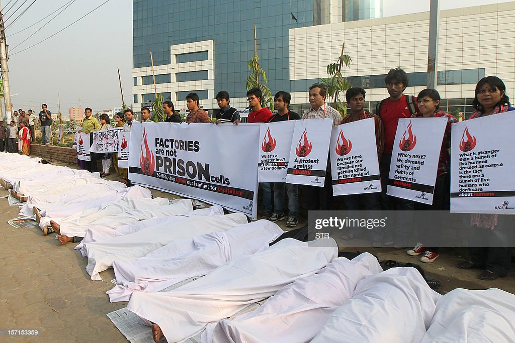 Bangladeshi activists pretend to be dead, wrapped in blankets, following a deadly fire in a garment factory during a protest in Dhaka on November 29, 2012. Police arrested three managers of Tazreen Fashion factory hit by a fire, following charges that they stopped workers from leaving the burning plant when the fire alarm sounded, insisting that it was just a routine drill, referring to a weekend blaze at a local garment factory that left 110 people dead and more than 100 injured. AFP PHOTO/STR