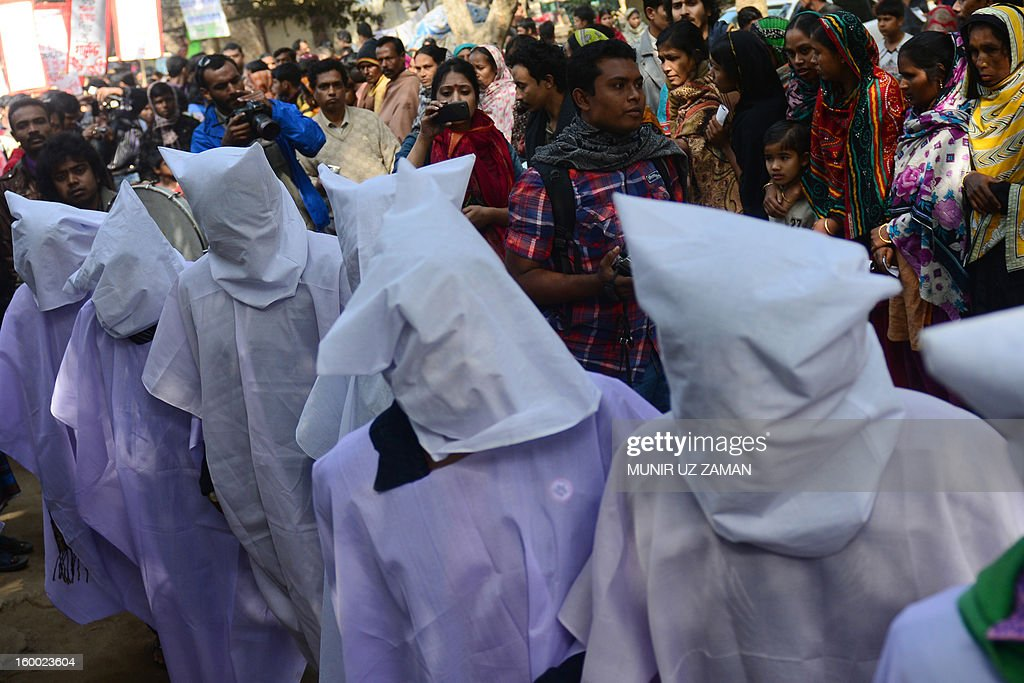 Bangladeshi activists wear death shrouds during a protest demanding punishment for the Tazreen Fashion factory owner and compensation for the victims of the 2012 factory fire, in Savar, some 30 kilometres north of Dhaka on January 25, 2013. At least 124 people were killed in a massive blaze which engulfed the multi-storey garment factory on the outskirts of the Bangladesh capital in one of the worst fire tragedies in the country on November 25, 2012. AFP PHOTO/Munir uz ZAMAN