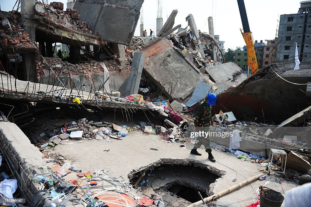 A Bangladeshi Army member looks into a hole made to recover survivors and dead bodies in the rubble of an eight-storey building that collapsed in Savar, on the outskirts of Dhaka on April 28, 2013. Four people were hauled out alive overnight more than 90 hours after the disaster, but the last feeble cries for help, still audible from inside the mountain of rubble early in the day, appeared to have ended. Rescue teams at the site of a collapsed factory block in Bangladesh where 363 people have died called in heavy-lifting equipment as hopes of finding more survivors faded. AFP PHOTO/ Munir uz ZAMAN