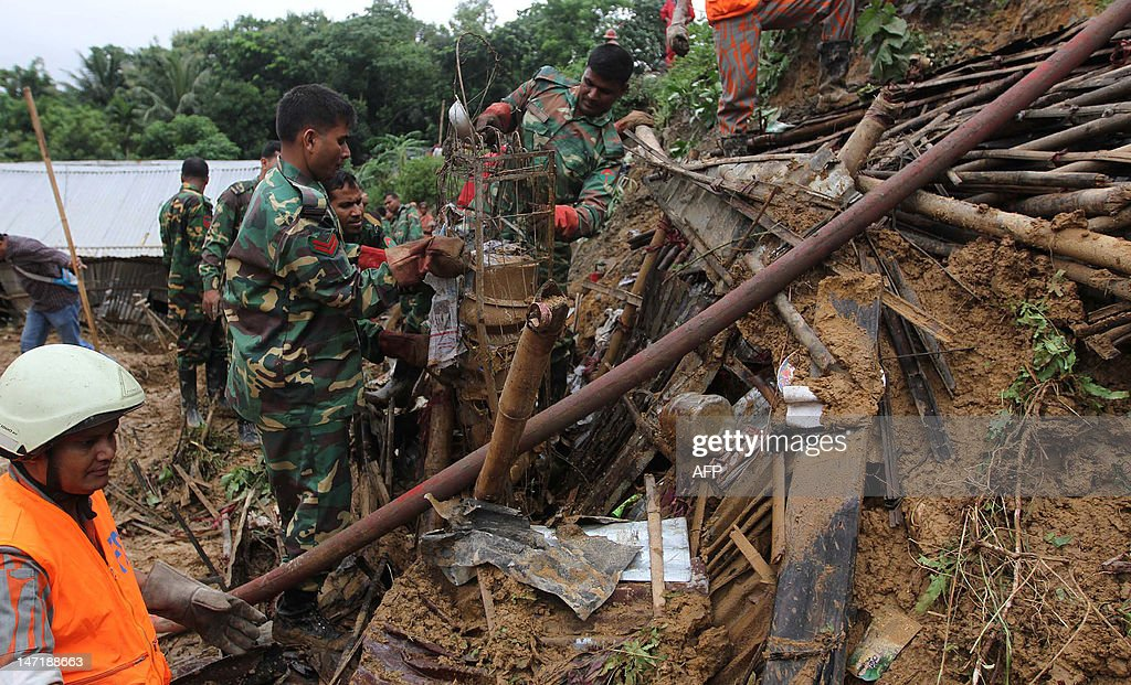 Bangladeshi army members clear debris while searching for bodies after a landslide in Chittagong on June 27, 2012. Nearly 90 people have been killed in landslides in southeast Bangladesh after three days of rains that triggered flash floods and severed transport links, officials said.