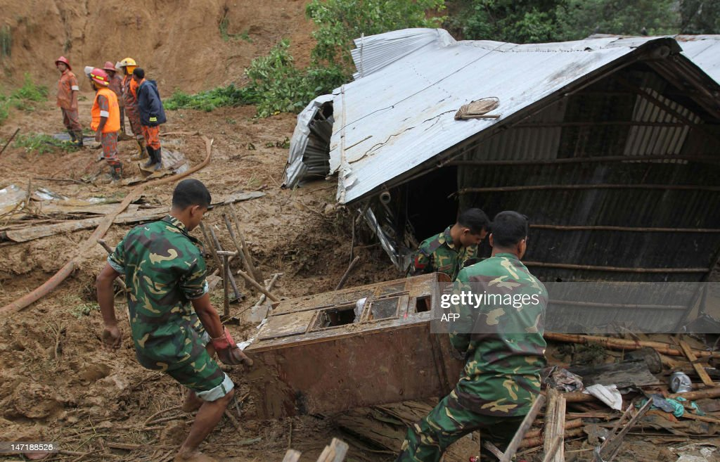 Bangladeshi army members move a piece of furniture while searching for bodies after a landslide in Chittagong on June 27, 2012. Nearly 90 people have been killed in landslides in southeast Bangladesh after three days of rains that triggered flash floods and severed transport links, officials said.