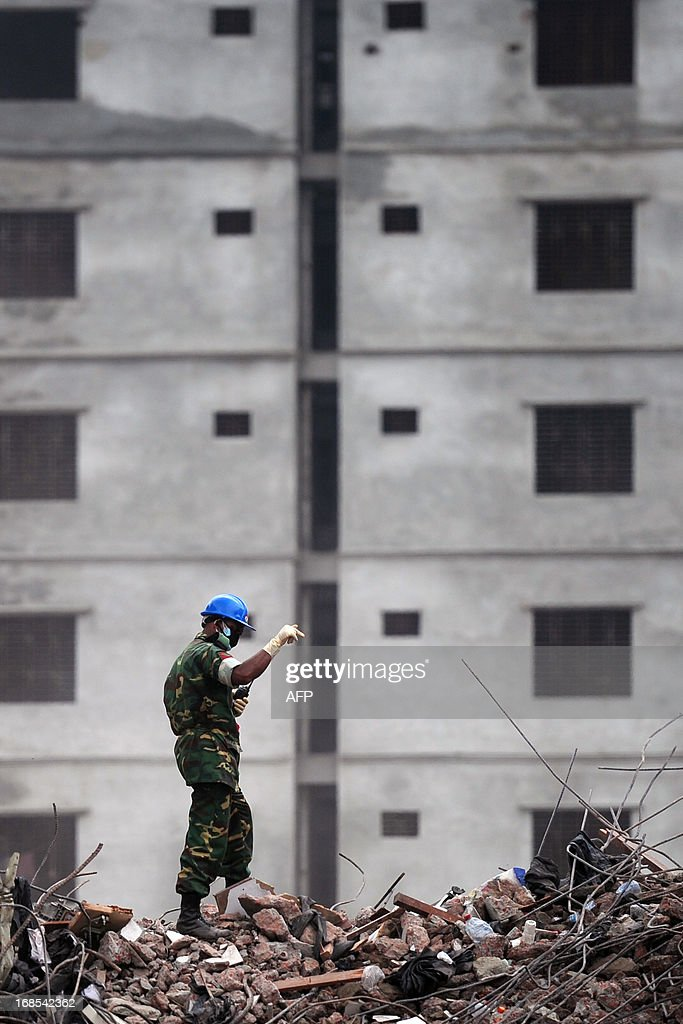 A Bangladeshi Army official gestures as he guides an excavator operator to removes debris as they continue the second phase of the rescue operation using heavy equipment after an eight-storey building collapsed in Savar, on the outskirts of Dhaka, on May 11, 2013. Bangladeshi doctors treating a 'miracle' survivor pulled from ruins of a collapsed building after 17 days said that she was doing 'great' and had been reunited with her family. Reshma, 18, a seamstress dug out from the rubble of the garment factory complex, 'never gave up hope' she would be rescued from the ruins of one of the world's worst industrial disasters, army doctor Fakrul Islam told AFP. AFP PHOTO/Munir uz ZAMAN