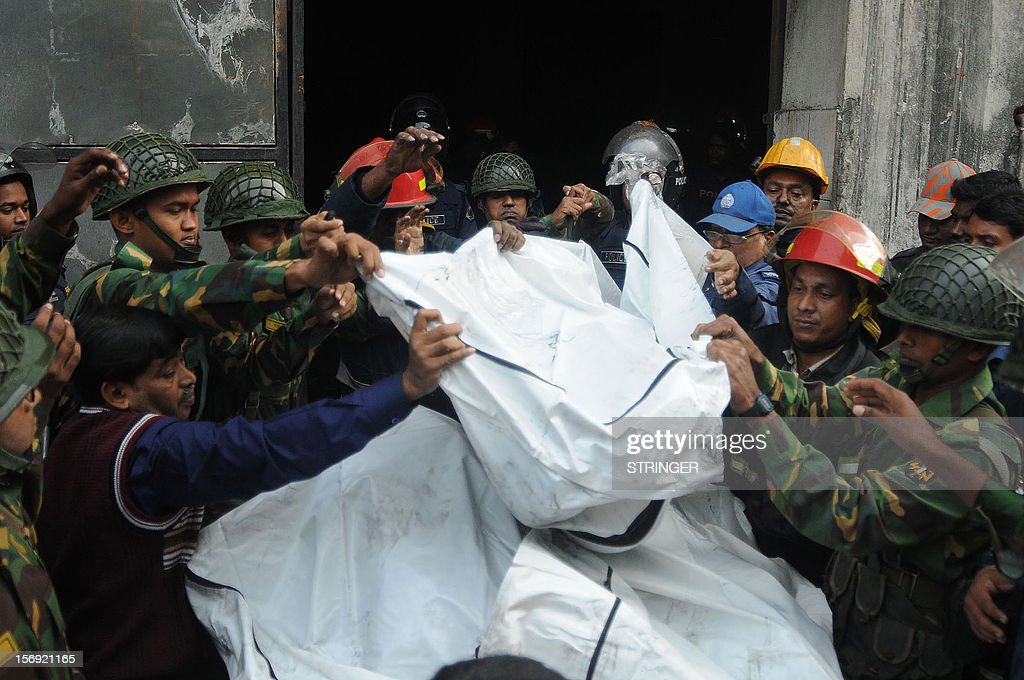 Bangladeshi Army personel carry the bodies of victims who died in a fire in the nine-storey Tazreen Fashion plant in Savar, about 30 kilometres north of Dhaka on November 25, 2012. Rescue workers in Bangladesh recovered 109 bodies on Sunday after a fire tore through a garment factory, forcing many workers to jump from high windows to escape the smoke and flames. AFP PHOTO
