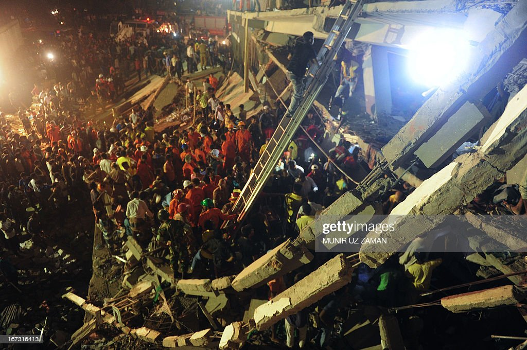 Bangladeshi Army personnel and civilian volunteers work on the scene at a building collapse in Savar, on the outskirts of Dhaka, on April 24, 2013. An eight-storey building containing several garment factories collapsed in Bangladesh, killing at least 82 people and further highlighting safety problems in the clothing industry. Armed with concrete cutters and cranes, hundreds of fire service and army rescue workers struggled to find survivors in the mountain of concrete and mangled steel, which resembled the aftermath of an earthquake. AFP PHOTO/ Munir uz ZAMAN