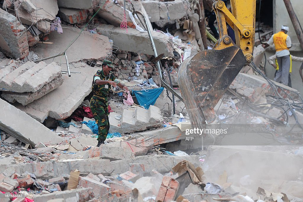 A Bangladeshi Army soldier directs an excavator as volunteers and rescue workers conduct rescue operations after an eight-storey building collapsed in Savar, on the outskirts of Dhaka, on April 26, 2013. A total of 304 people are so far known to have died after the eight-storey building collapsed in the town of Savar on April 24. Rescuers are racing against time to find more survivors in searing temperatures, watched on by hundreds of anxious relatives waiting for news of their missing loved ones. AFP PHOTO/ MUNIR UZ ZAMAN