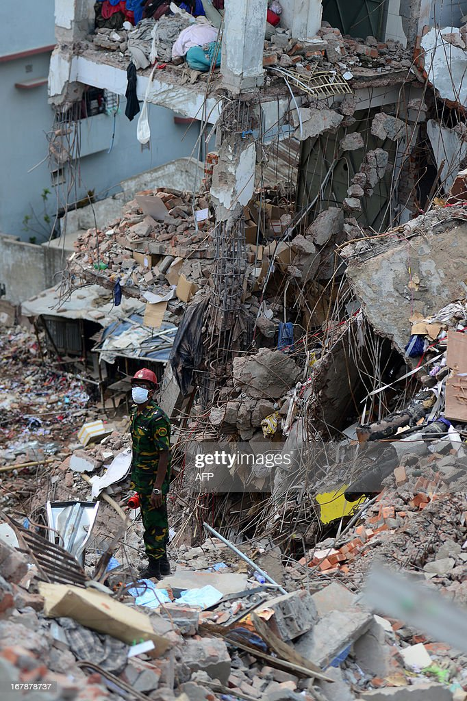 A Bangladeshi Army soldier looks as the second phase of a rescue operation using heavy equipment continues after an eight-storey building collapsed in Savar, on the outskirts of Dhaka, on May 2, 2013. Bangladesh authorities have suspended the mayor of Savar satellite town outside the capital for approving the faulty construction of a building that collapsed last week, killing 429 people. AFP PHOTO/ Munir uz ZAMAN
