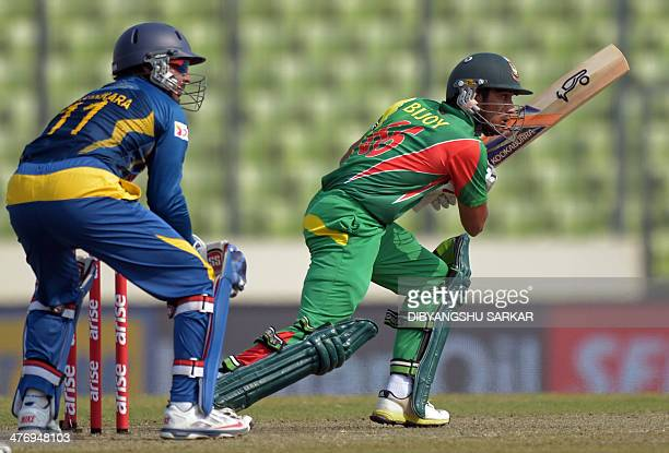 Bangladeshi batsman Anamul Haqu plays a shot as Sri Lankan wicketkeeper Kumar Sangakkara looks on during the tenth match of the Asia Cup oneday...