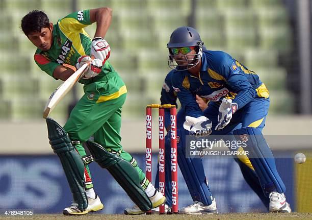 Bangladeshi batsman Anamul Haque plays a shot as Sri Lankan wicketkeeper Kumar Sangakkara looks on during the tenth match of the Asia Cup oneday...