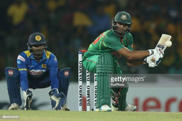 Bangladeshi batsman Mohammad Mahmudullah plays a shot in front of Kusal Perera during the first Twenty20 cricket match between Bangladesh and Sri...