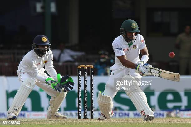 Bangladeshi batsman Sabbir Rahman right plays a shot as Sri Lanka's wicket keeper Niroshan Dickwella looks on against Sri Lanka during the second day...