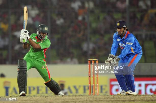 Bangladeshi batsman Shakib Al Hasan plays a shot as the Indian captain Mahendra Singh Dhoni looks on during the one day international Asia Cup...
