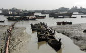 A Bangladeshi boatman pushes a boat laden with sand across a channel in the port area of Chittagong on January 1 2009 Bangladesh's former premier...