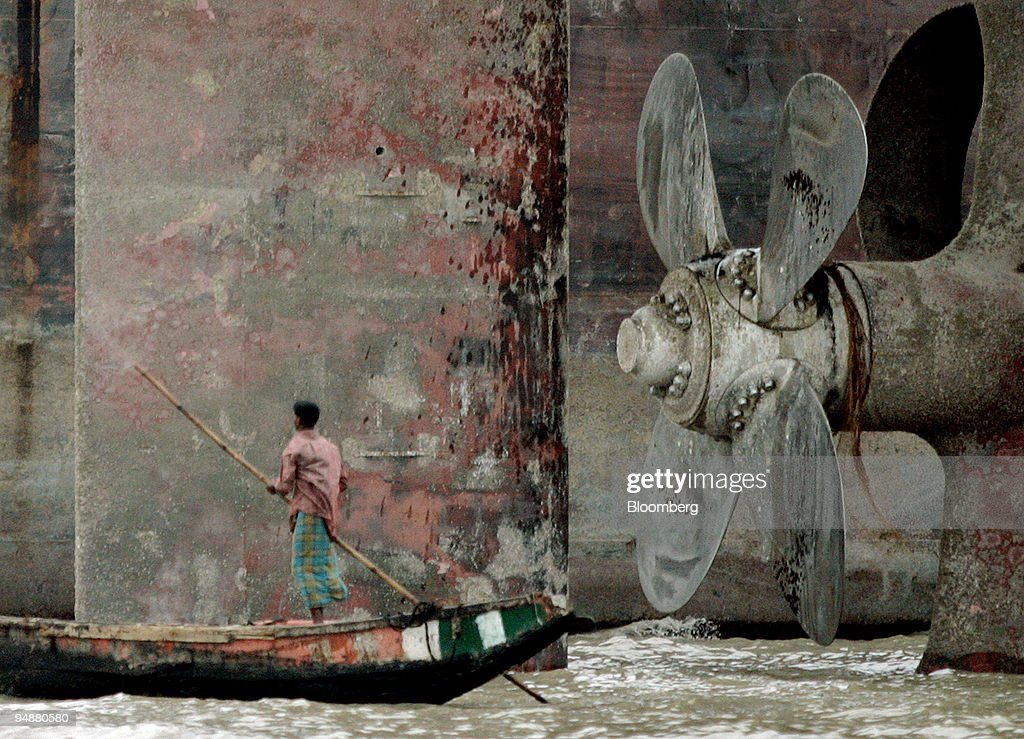 Bangladeshi boatman pushes his craft past the propeller and rudder of a beached freighter May 1 2005 at a yard near Chittagong Scrapped ships end up...