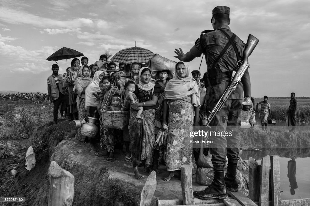 COX'S BAZAR, BANGLADESH - NOVEMBER 02: A Bangladeshi border guard from the BGB gestures as he controls a crowd of Rohingya Muslim refugees waiting to proceed to camps after crossing the border from Myanmar into Bangladesh near the Naf River on November 2, 2017 near Anjuman Para in Cox's Bazar, Bangladesh. More than 600,000 Rohingya refugees have flooded into Bangladesh to flee an offensive by Myanmar's military that the United Nations has called 'a textbook example of ethnic cleansing'. The refugee population continues to swell further, with thousands more Rohingya Muslims making the perilous journey on foot toward the border, or paying smugglers to take them across by water in wooden boats. Hundreds are known to have died trying to escape, and survivors arrive with horrifying accounts of villages burned, women raped, and scores killed in the 'clearance operations' by Myanmar's army and Buddhist mobs that were sparked by militant attacks on security posts in Rakhine state on August 25, 2017. What the Rohingya refugees flee to is a different kind of suffering in sprawling makeshift camps rife with fears of malnutrition, cholera, and other diseases. Aid organizations are struggling to keep pace with the scale of need and the staggering number of them - an estimated 60 percent - who are children arriving alone. Bangladesh, whose acceptance of the refugees has been praised by humanitarian officials for saving lives, has urged the creation of an internationally-recognized 'safe zone' where refugees can return, though Rohingya Muslims have long been persecuted in predominantly Buddhist Myanmar. World leaders are still debating how to confront the country and its de facto leader, Aung San Suu Kyi, a Nobel Peace Prize laureate who championed democracy, but now appears unable or unwilling to stop the army's brutal crackdown.