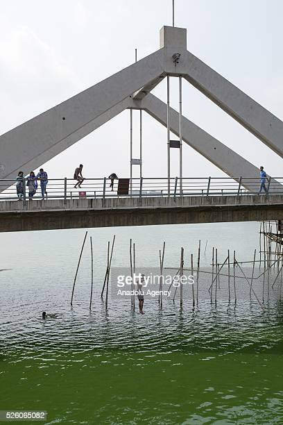 Bangladeshi boy jumps to the Hatirjheel Lake to cool himself during a hot day in Dhaka Bangladesh on April 29 2016