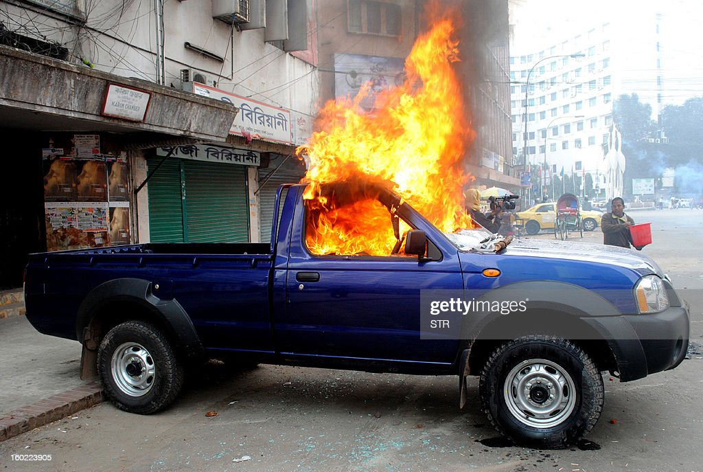 A Bangladeshi bystander uses a bucket to try and put out a fire on a police car allegedly set fire to by Jamaat-e-Islami members in Dhaka on January 28, 2013. Thousands of student activists from Bangladesh's largest Islamic party clashed with police, throwing petrol bombs and bricks to protest at the trial of their leaders for alleged war crimes.