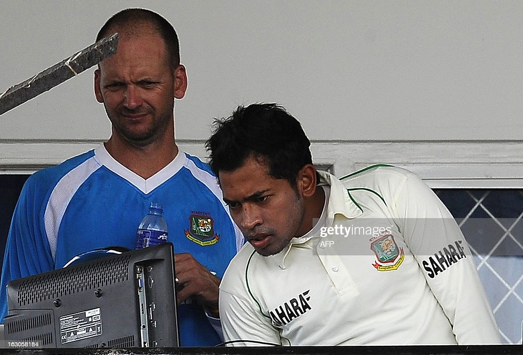 Bangladeshi captain Mushfiqur Rahim (R) and coach Shane Jurgensen look at a laptop as they sit in the dressing room after rain stopped play during the second day of a three day practice match between the Sri Lanka Development Emerging Team and Bangladesh at the Uyanwatte Stadium in Matara on March 4, 2013. AFP PHOTO/ LAKRUWAN WANNIARACHCHI