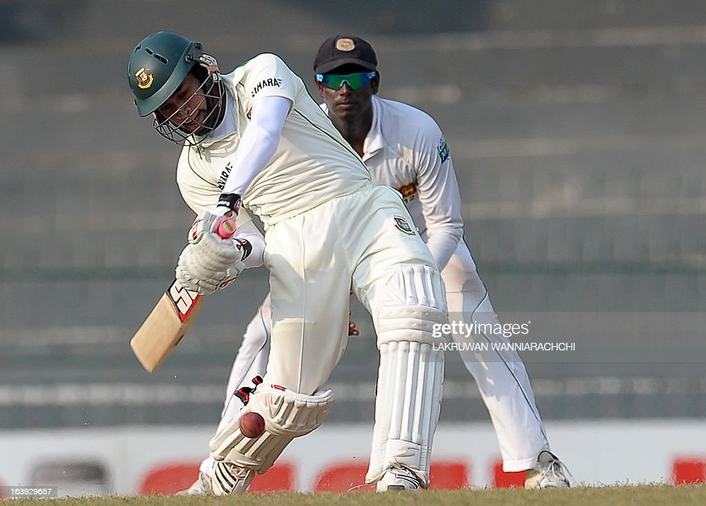 Bangladeshi captain Mushfiqur Rahim (L) plays a shot as Sri Lankan captain Angelo Mathews look on during the third day of their second Test match between Sri Lanka and Bangladesh at the R. Premadasa Cricket Stadium in Colombo on March 18, 2013.