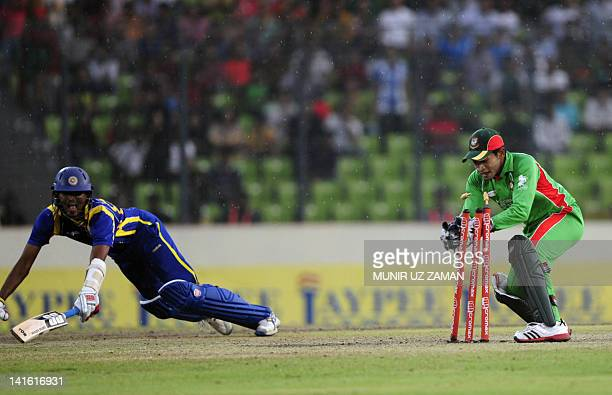 Bangladeshi captain Mushfiqur Rahim tries to break the stumps as the Sri Lankan batsman Suranga Lakmal tries to make his ground during the one day...