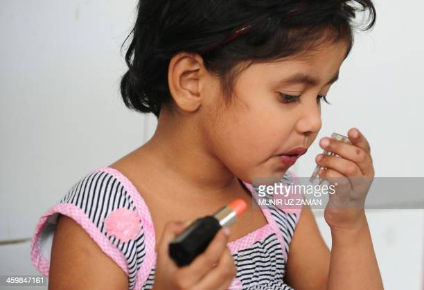 A Bangladeshi child applies lipstick as she waits for a train with her parents at the railway station during an ongoing blockade organised by...