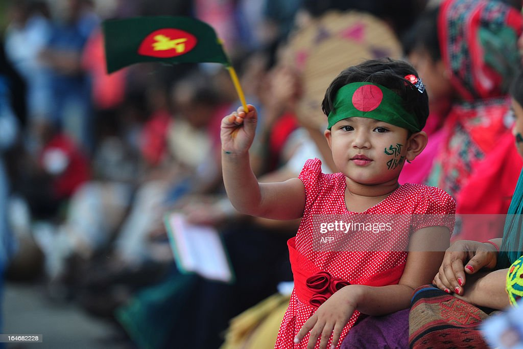 A Bangladeshi child holds a national flag as she attends a rally with her mother to mark the 42nd anniversary of independence in Dhaka on March 26, 2013. Bangladesh is commemorating the 42nd anniversary of its independence and set up a special tribunal on March 25, to try people accused of committing war crimes during the country's bloody 1971 liberation struggle against Pakistan. AFP PHOTO/Munir uz ZAMAN