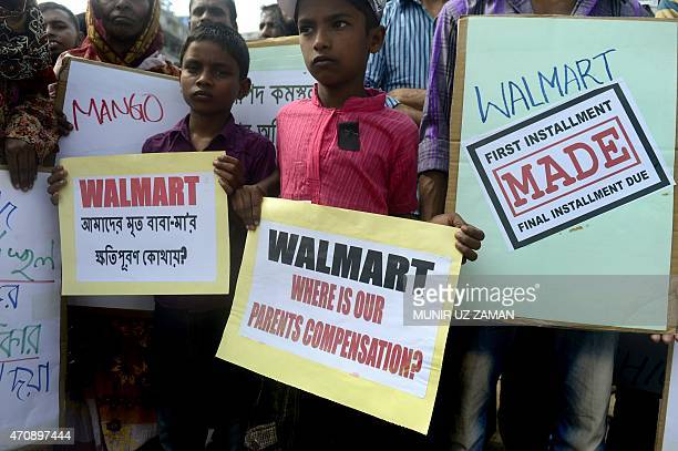 Bangladeshi children of victims of the Rana Plaza building collapse hold placards as they mark the second anniversary of the disaster at the site...