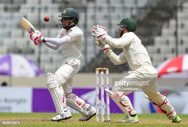 Bangladeshi cricket captain Mushfiqur Rahim plays a shot as the Australian wicketkeeper Matthew Wade looks on during the third day of the first Test...