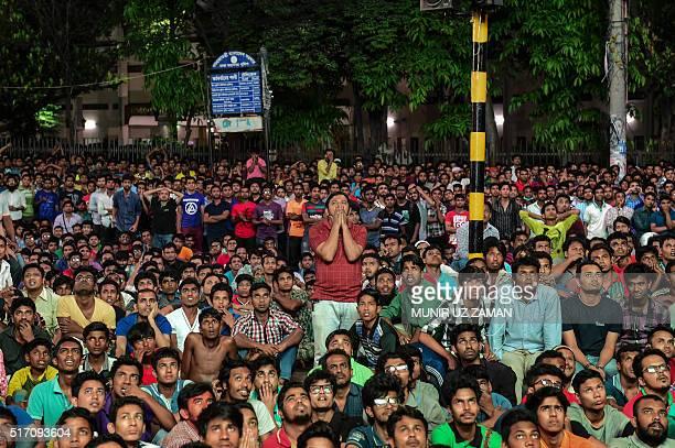 Bangladeshi cricket fans cheers as they watch the World T20 cricket tournament match between Bangladesh and India broadcast on a screen in a street...