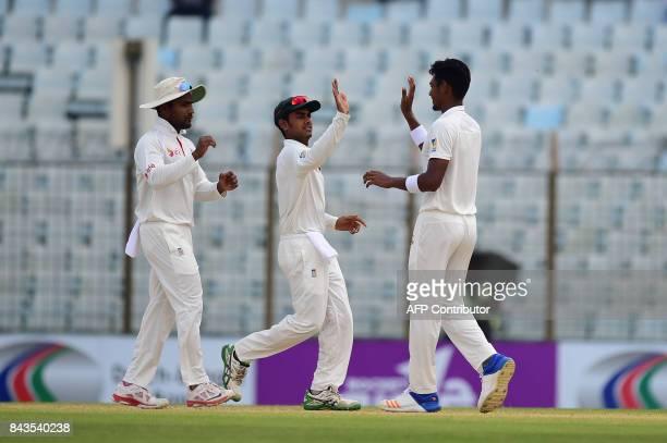 Bangladeshi cricketer Mehidy Hasan congratulates teammate Mustafizur Rahman after the dismissal of Australian cricketer Nathan Lyon during the fourth...