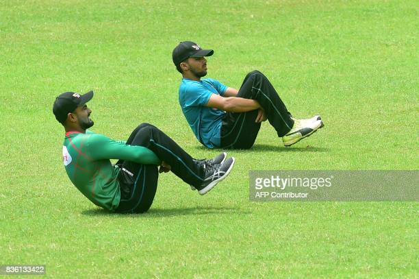 Bangladeshi cricketer Mominul Haque stretches next to a teammate during a training session at the ShereBangla National Cricket Stadium in Dhaka on...