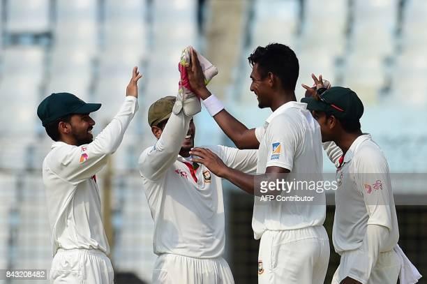 Bangladeshi cricketer Mustafizur Rahman celebrates with his teammates after the dismissal of the Australian cricketer David Warner during the third...