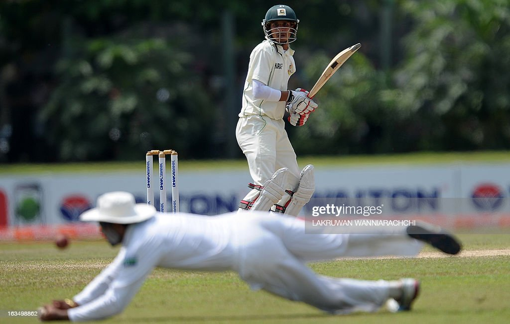 Bangladeshi cricketer Nasir Hossain (C) watches as Sri Lankan cricketer Tillakaratne Dilshan drops a catch during the fourth day of the opening Test match between Sri Lanka and Bangladesh at the Galle International Cricket Stadium in Galle on March 11, 2013. AFP PHOTO/ LAKRUWAN WANNIARACHCHI