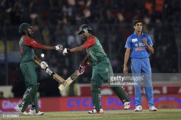 Bangladeshi cricketer Soumya Sarkar celebrates with his teammate Tamim Iqbal after hitting a boundery as the Indian cricketer Ashish Nehra looks on...