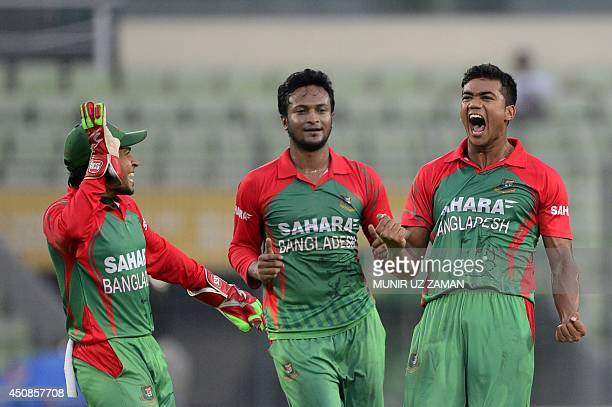 Bangladeshi cricketer Taskin Ahmed celebrates with captain Mushfiqur Rahim and teammate Shakib Al Hasan after the dismissal of Indian cricketer...
