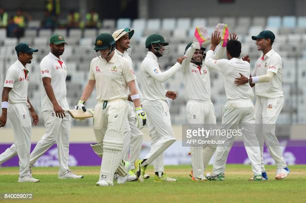 Bangladeshi cricketers celebrate after the dismissal of Australian cricket captain Steven during the second day of the first Test cricket match...